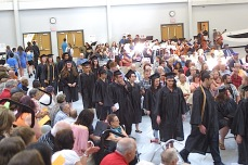 """Graduates return to their seats after performing """"Somewhere Over the Rainbow"""" on memory of Evelyn Miller. —Photo by Chris Baldus"""