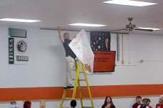 Charles City High School associate principal Larry Wolfe hangs the Class of 2021 banner in the high school commons Friday morning.